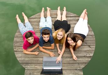 Gruppe Jugendliche mit Notebook / Laptop draußen am See