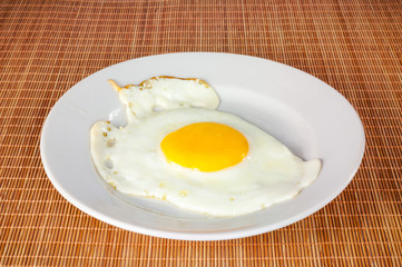 Fried egg in a white plate on a bamboo cover
