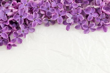 Purple lilac flowers on white textile