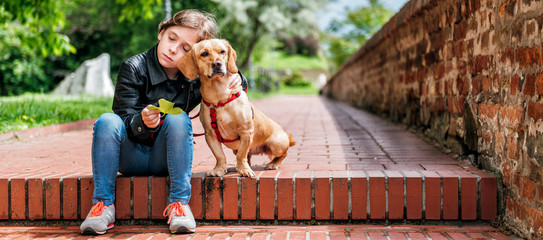 Girl with the dog sitting on the stairs