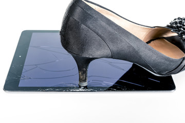 Shoe stepping on broken iPad cracked glass screen