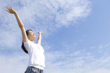 青空の下で手を広げる女性