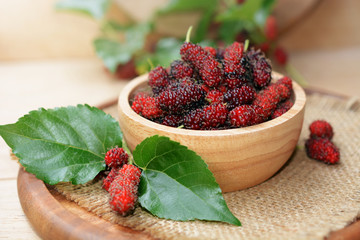 fresh organic mulberry in bowl on wooden background with mulberry fruit and mulberry branch.