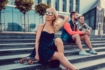 Blond female on longboard and two males posing.