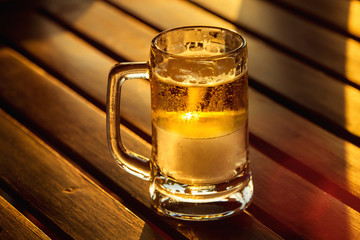 A glass of golden beer with ice at wooden tablre