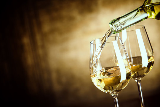 Pouring two glasses of white wine from a bottle