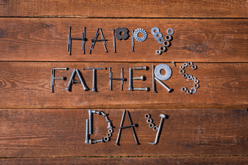 Happy Father's Day. Greeting card made of metallic bolts and iron nails