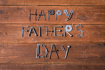 Happy father's Day! Greeting gard made of tools, iron nuts and bolts. Wooden background