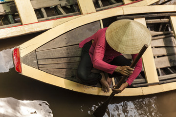 Vietnamese old woman with typical conical hat in a wood boat. Top view