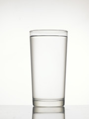 Clear glass with full of water isolated on background.