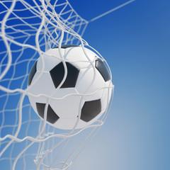 Fußball im Netz vom Tor vor Himmel