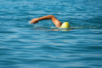 Man swimmer swimming crawl in blue sea.Training for triathlon
