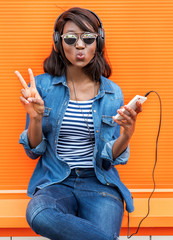 Beautiful smiling african woman with headphones listens to music