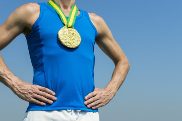 Athlete standing with gold medal hanging from a Brazil colors yellow and green ribbon against blue sky