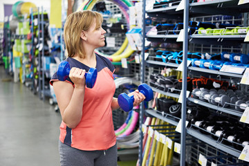 Woman chooses dumbbells for fitness in sports shop