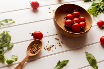 Seasonings, tomatoes and spices on white wooden background