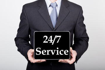 technology, internet and networking in business concept - businessman holding a tablet pc with 24 7 service sign. Internet technologies in business