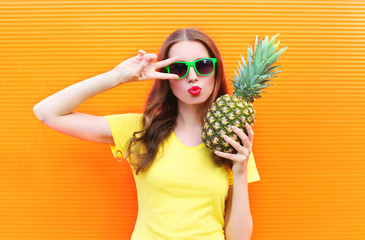 Fashion cool girl in sunglasses with pineapple over colorful ora