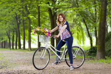 Beautiful young woman standing with a vintage bicycle at the par