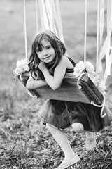 beautiful baby girl ride on a swing