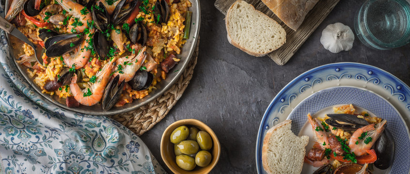 Plates with paella on the dark stone table with different accessories wide screen