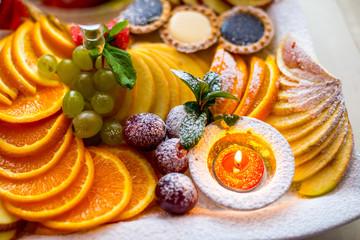 Cake with many fruits oranges, grapes, apple etc