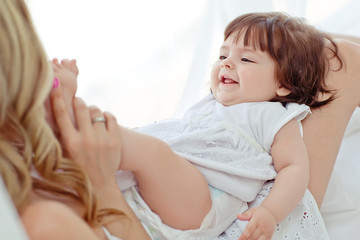 Happy mother with her funny baby on the bedroom