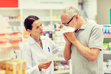 pharmacist and senior man with flu at pharmacy