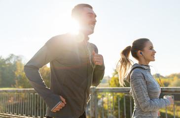 happy couple with earphones running outdoors