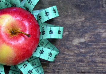 Fresh apple and measuring tape on wooden background.Healthy eating or diet concept.