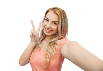 smiling woman taking selfie and showing peace sign