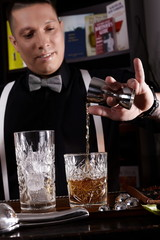 Young man working as a bartender in a nightclub/cocktail bar