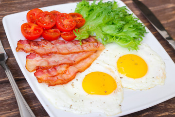 American Breakfast fried Eggs and bacon with tomato and lettuce on a wooden background