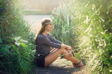 Young hippie woman sitting on the ground near green bushes and cactus
