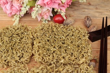 Dry instant vegetable noodle on wood background.