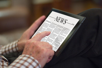 Old man reading the newspaper on a tablet
