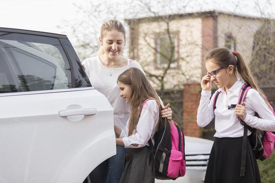 Cute schoolgirls getting in the car to ride to school