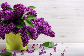 Still life. Bouquet purple lilacs in yellow a vase on a wooden table Spilled with petals