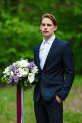 Young beautiful groom standing and holding wedding bouquet