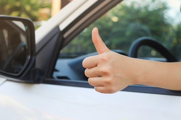 close up hand thumb up from car's window:good drive concept