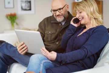 älteres paar mit laptop und telefon zu hause auf dem sofa