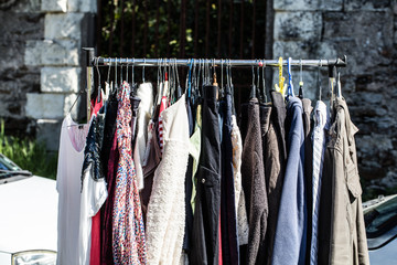 rack of old fashioned women's clothes at garage sale