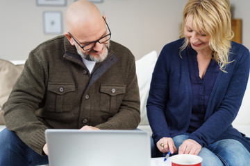 älteres paar sitzt auf dem sofa mit laptop und unterlagen
