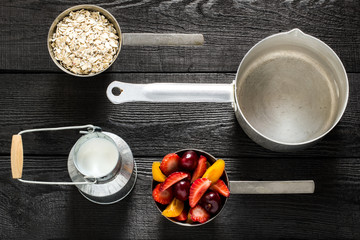 Utensils and ingredients for cooking oatmeal with milk and fruit