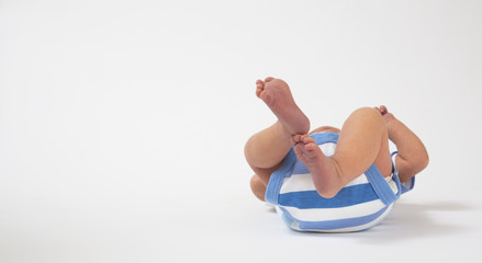 Newborn baby lying on its back on a white backdrop with blue en white stripes clothes on and his feet in the air.