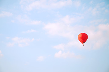 Red hot air baloon in blue sky with white clouds