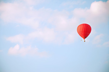 Poster Montgolfière / Dirigeable Red hot air balloon in blue sky with white clouds