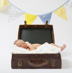 Newborn baby lying in a brown vintage suitcase on a white blanket sleeping