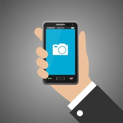 Hand holding smartphone with camera icon