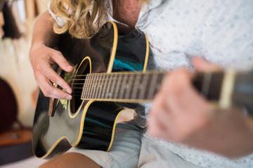 Young man plays guitar, closeup
